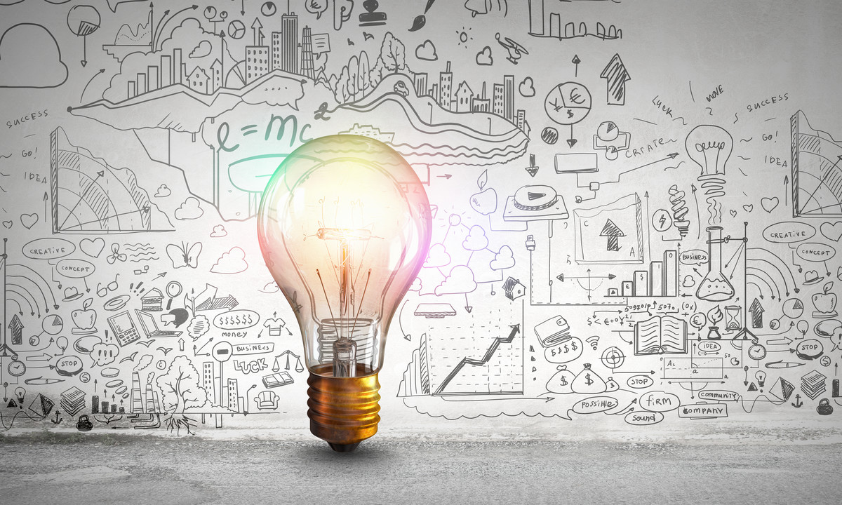 Glass glowing light bulb and business sketched ideas